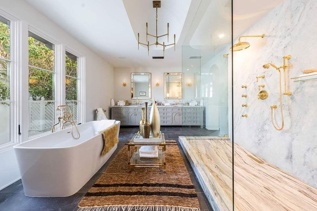 A bathroom with marble and gold finishes is pictured.