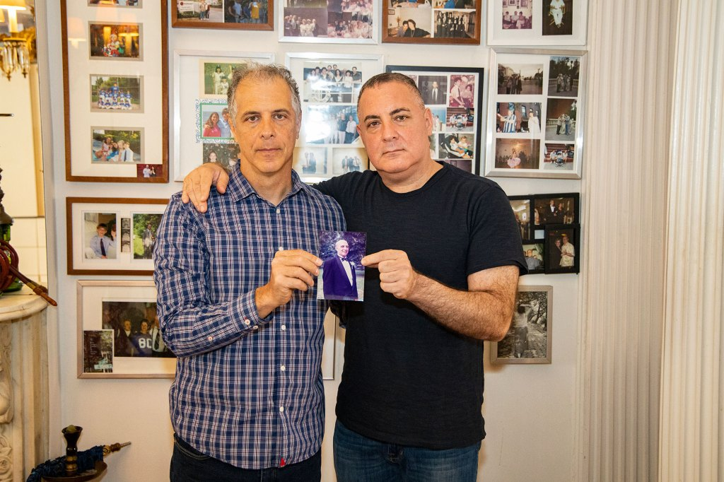 Peter Arbeeny (L) and Daniel Arbeeny (R) holding a photo of their father Norman Arbeeny inside their father's home at 128 Amity Street in Brooklyn, where their father passed away due to COVID-19.