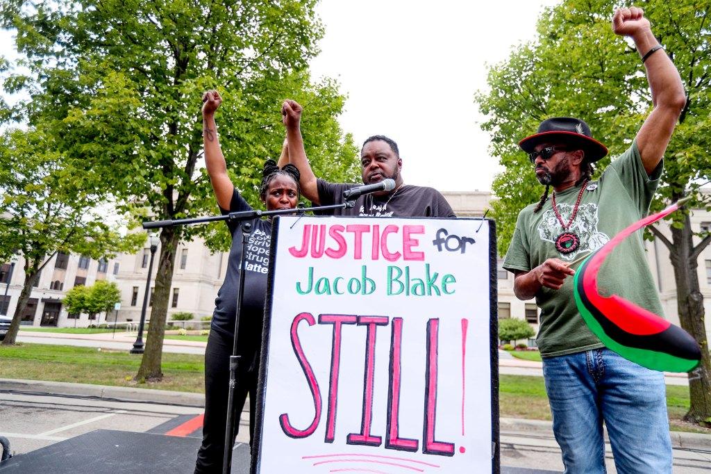 Letetra Widman, Jacob Blake's sister (left), Jacob Blake Sr. (center), and Justin Blake rally for Jacob Blake in Civic Center Park in Kenosha, Wisconsin on August 21, 2021.