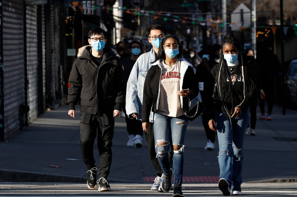 Pedestrians wear masks while crossing a street in Soho on March 21, 2021.