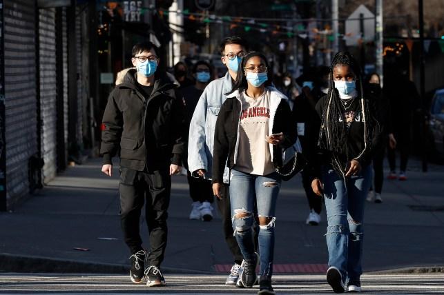 Pedestrians wear masks as they cross a street in Soho on March 21, 2021.