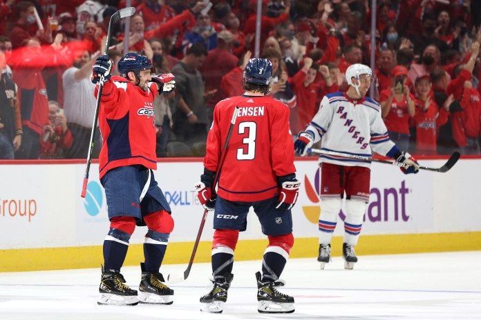 Alex Ovechkin of the Washington Capitals celebrates with a teammate after scoring a goal in a regular-season-opening win over the New York Rangers.