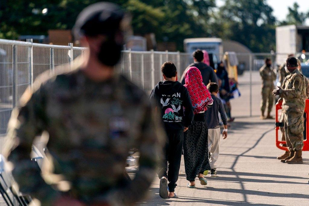 Afghan refugees walk through an Afghan refugee camp at Joint Base McGuire Dix Lakehurst, N.J.