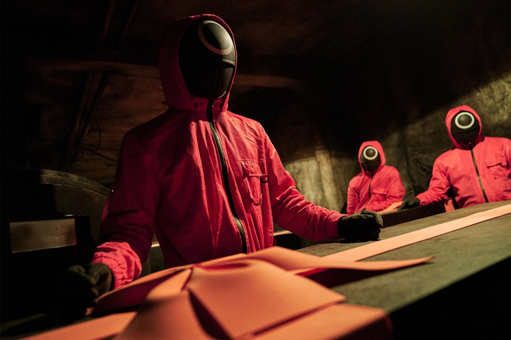 """A dark room full of shadowy figures wearing pink jumpsuits with black masks covering their faces in """"Squid Game."""""""
