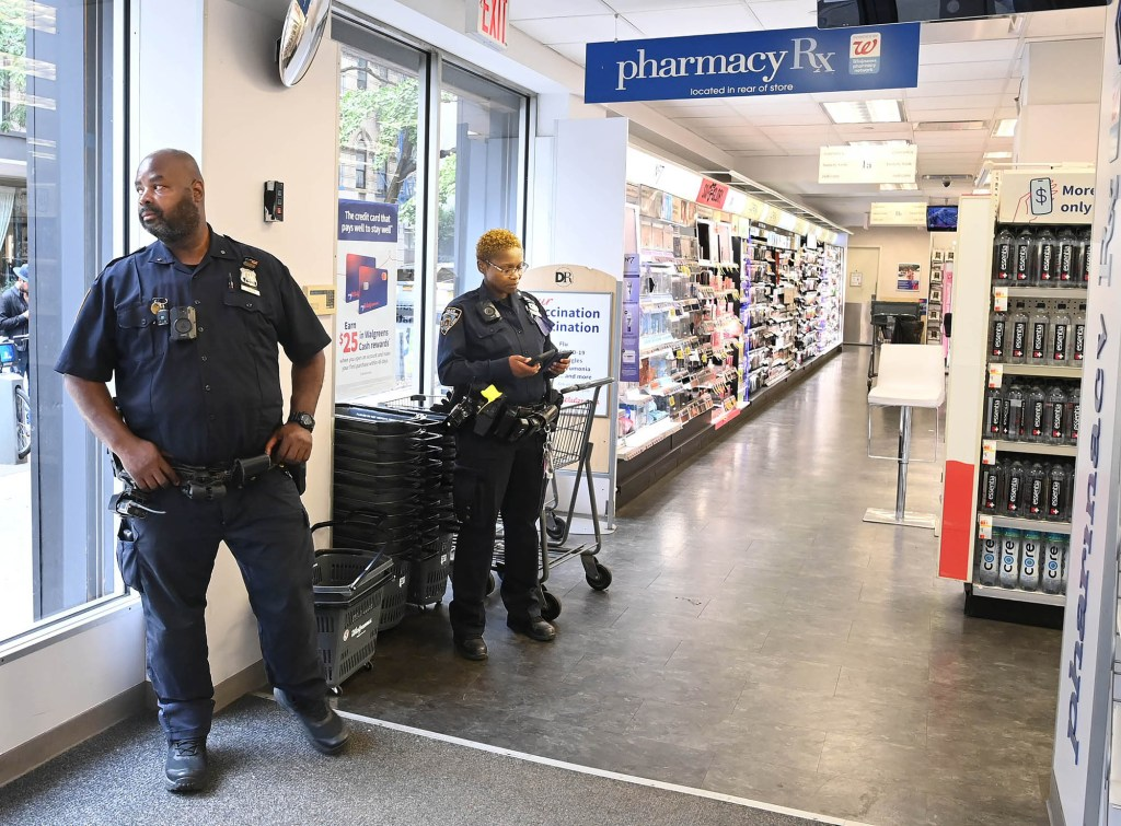 Ninth Precinct police officers stand guard inside the Duane Reade on Avenue B and East 2nd St., where certain items are kept locked.