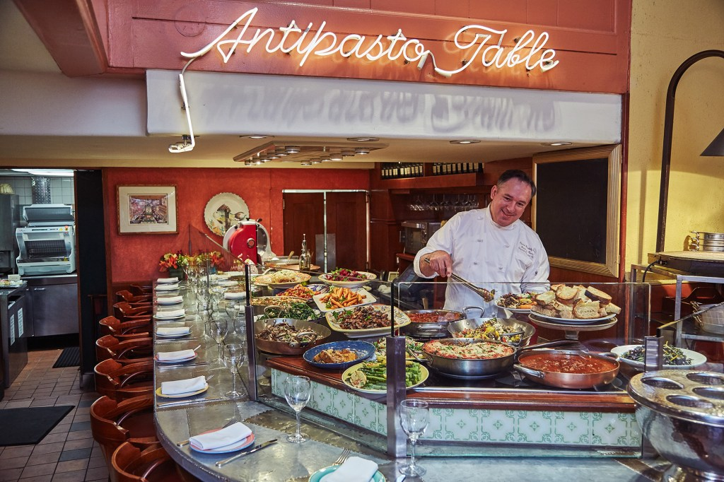 A man stands behind the antipasta table at Trattoria dell'Arte