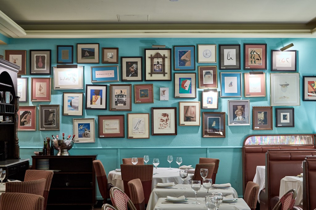 Interior of Trattoria dell'Arte with an array of framed photos on the wall and tables set for dining