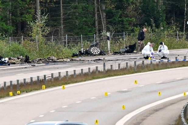 Forensic technicians work at the scene after a traffic accident between a car and a lorry killed three people including Lars Vilks.