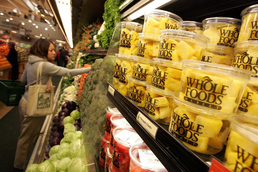Customer shops for produce at a Whole Foods