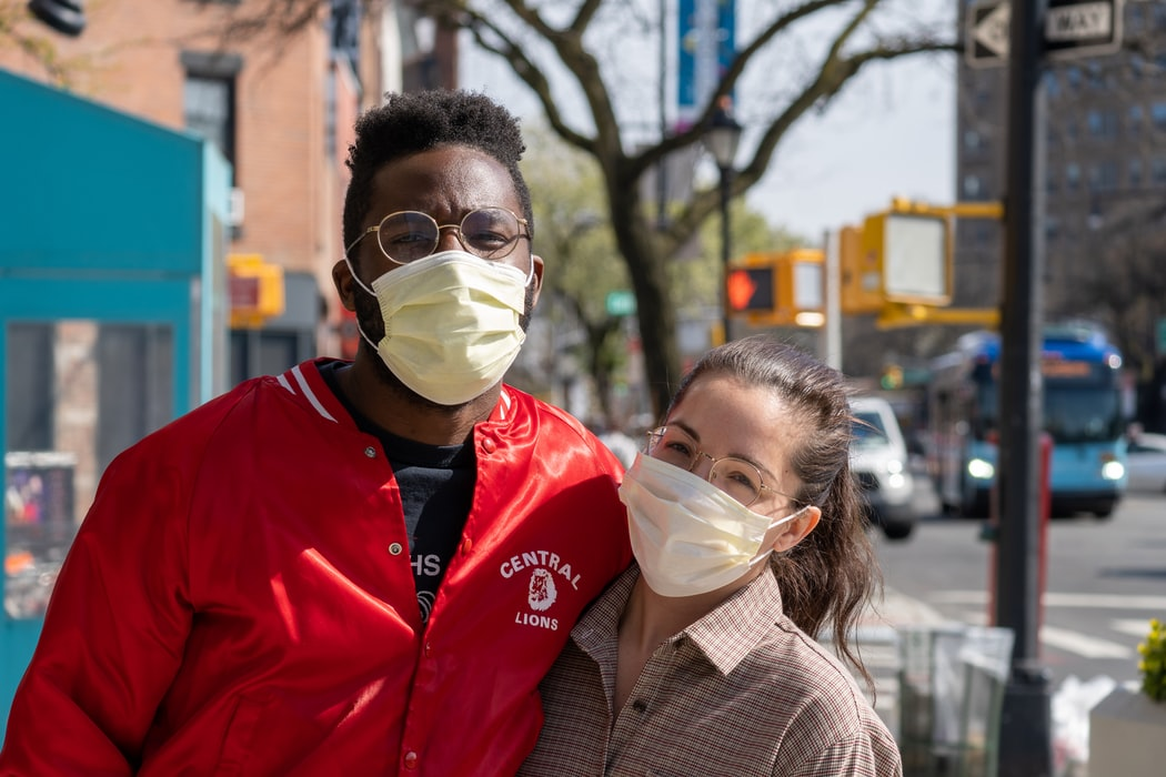 two people posing for a photo wearing face masks due to Covid-19