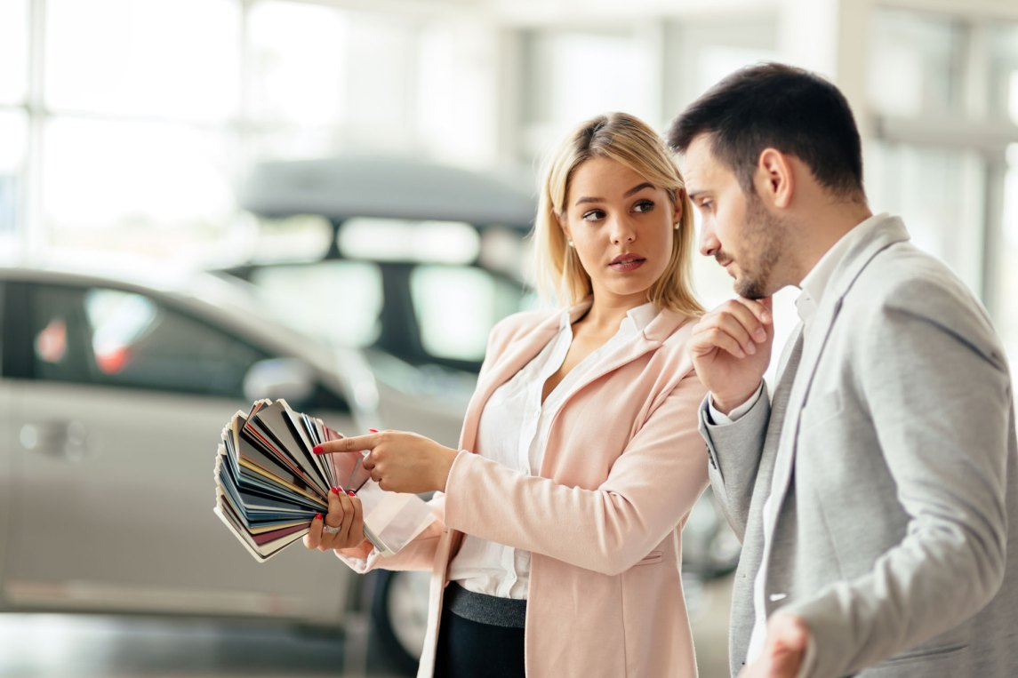 woman picking a car color from swatches with a car salesman