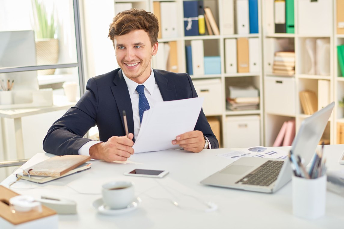 happy businessman sitting at a desk with a computer