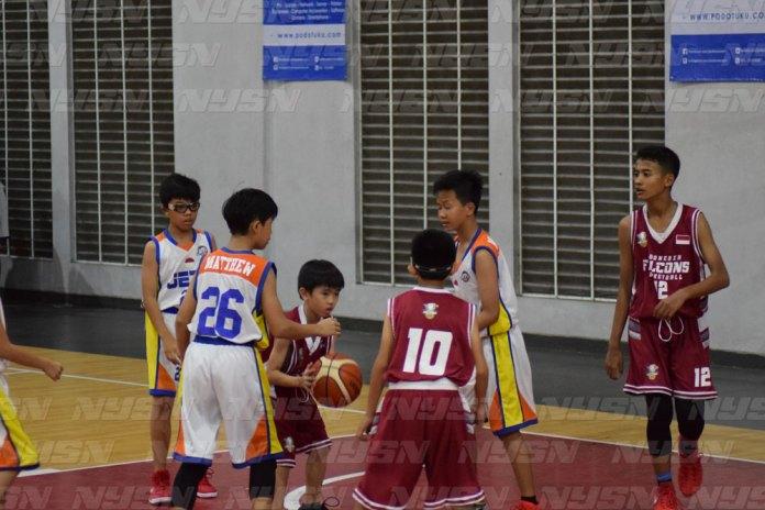 Salah satu pemain Indonesia Falcon (merah) berusaha melindungi bola dari pemain Jetz Basketball Club.