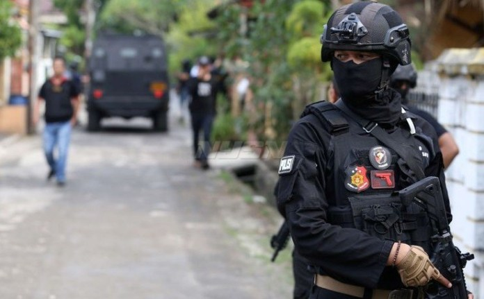 Petugas Densus 88 tengah berjaga di sekitar rumah terduga teroris di Kawasan Perumahan Kunciran Indah pada akhir pekan lalu. (kompas.com)