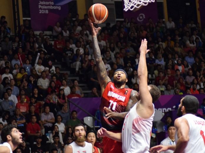 Terjadi duel udara antara pemain Timnas Indonesia, Jamarr Andre Johnson (Merah/71) dan Khalil Khouri (putih/00), dalam fase play off 5-8 Asian Games 2018, Selasa (28/8), di Basket Hall Gelora Bung Karno. Indonesia akhirnya takluk 66-76. (Riz/NYSN)