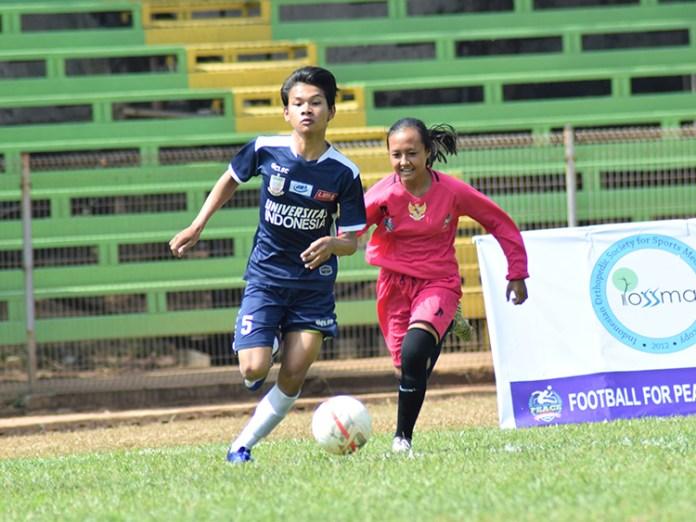 Pemain Universitas Indonesia (Biru) berusaha melewati pemain JKT 69 (Pink)