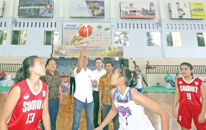Ketua Umum KONI Sumut, John Ismadi Lubis (tengah), melakukan pelemparan bola pertama disaksikan Ketua Panitia yang juga Waketum Perbasi Sumut, Iwan Hartono Alam (dua kiri), saat pembukaan Kejurnas Bola Basket Junior KU14 dan KU16, di GOR UNPRI, di Medan, pada Kamis (10/1). (harian.analisadaily.com)