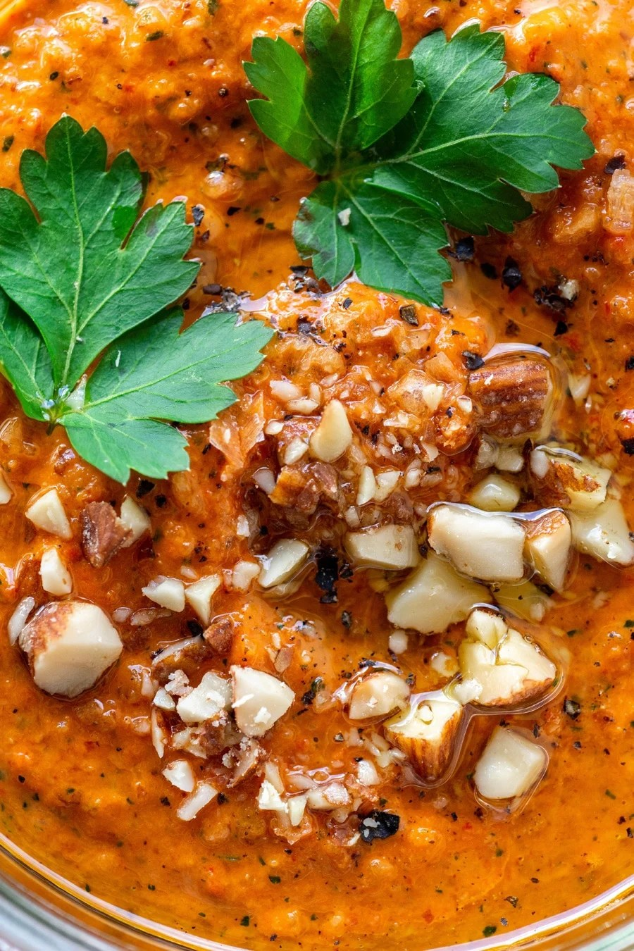 A close up view of bright orange romesco sauce topped with parsley leaves, chopped almonds, and black pepper