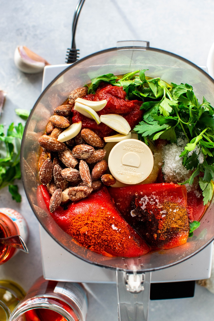 Overhead view of a food processor filled with all the ingredients for this fast and easy romesco sauce - roasted red peppers, almonds, garlic, parsley, spices, and salt.