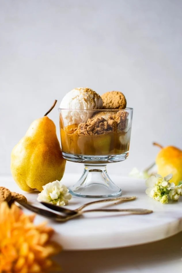 These cardamom caramel and pear cookie crumble cups are made with fragrant pears simmered in a cardamom and cinnamon spiced coconut sugar caramel. Served with your favorite dairy free vanilla ice cream and Simple Mills crunchy toasted pecan cookies. A crazy delicious seasonal dessert that is naturally sweetened, vegan and paleo friendly!