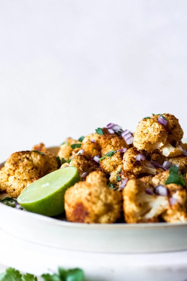 Mexican roasted cauliflower might just become your new favorite veggie side dish. Cauliflower florets tossed with some flavorful spices and roasted until crispy and caramelized, served with a healthy squeeze of lime juice, cilantro, red onion, and maybe even some avocado for good measure. Gluten free, paleo, vegan, AND whole30 friendly!
