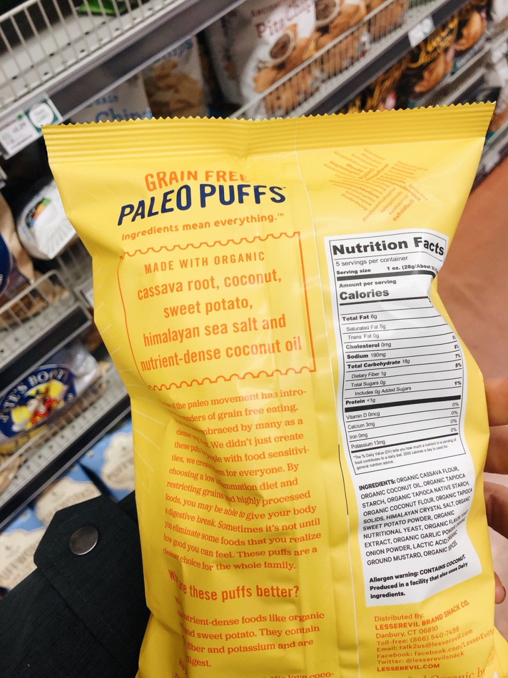 """Holding a bag of Lesser Evil Grain Free Paleo """"cheese"""" puffs in the grocery store with ingredients showing"""