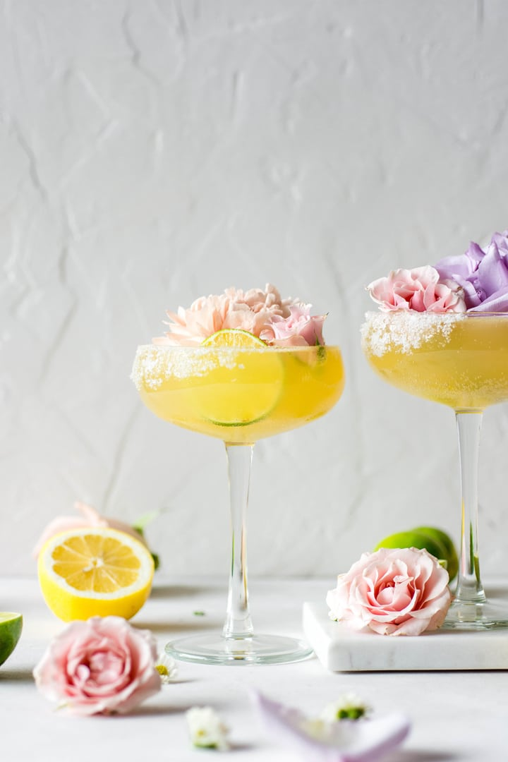 A side view of two bright yellow kombucha margarita served up with a big pink flower and a lime wheel.