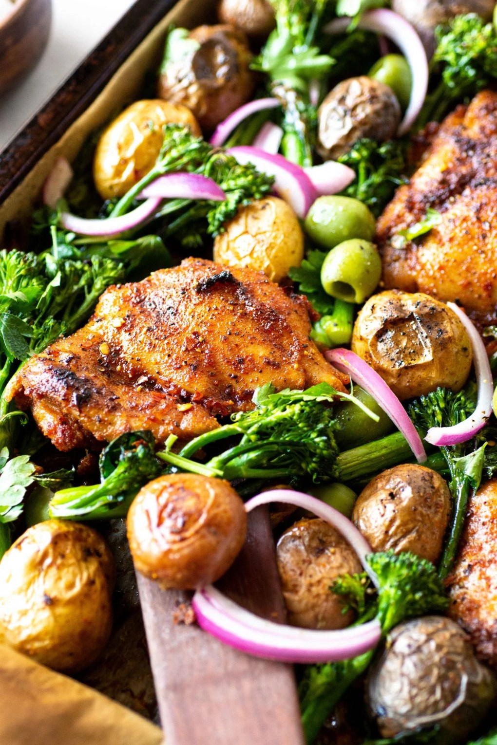 A 45 degree view of a roasting tray with spiced chicken thighs, potatos, broccolini, olives, and pickled red onions