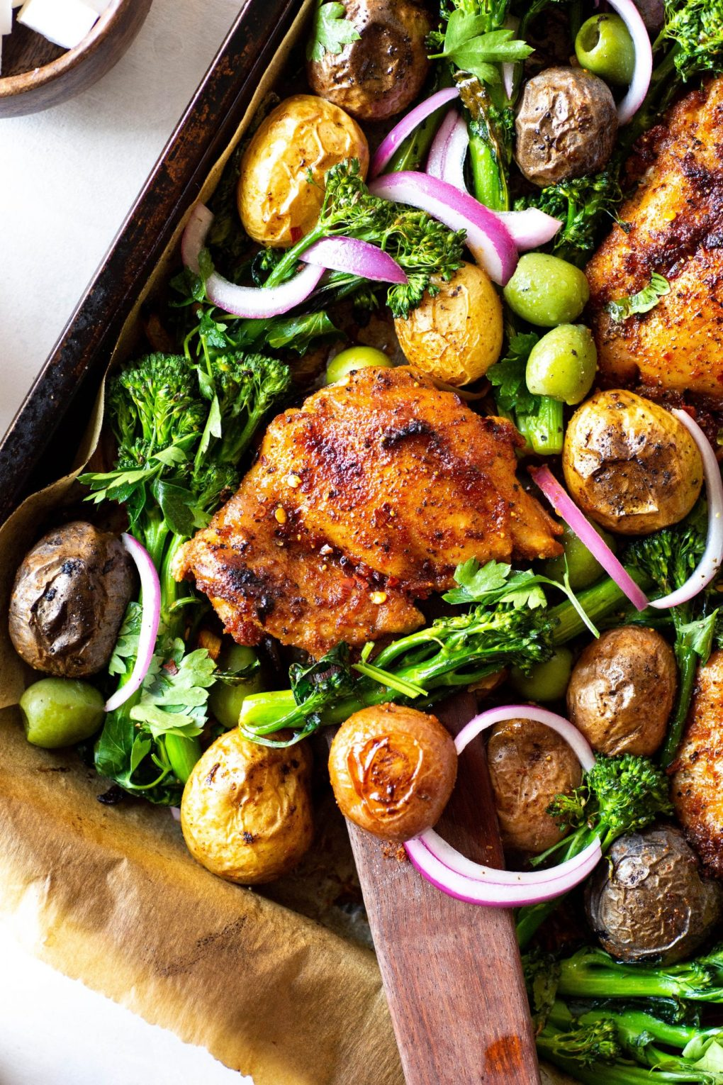 Overhead view of of an angled roasting tray with spiced chicken thighs, potatos, broccolini, olives, and pickled red onions. On a white background next to a small wooden bowl of feta cheese.