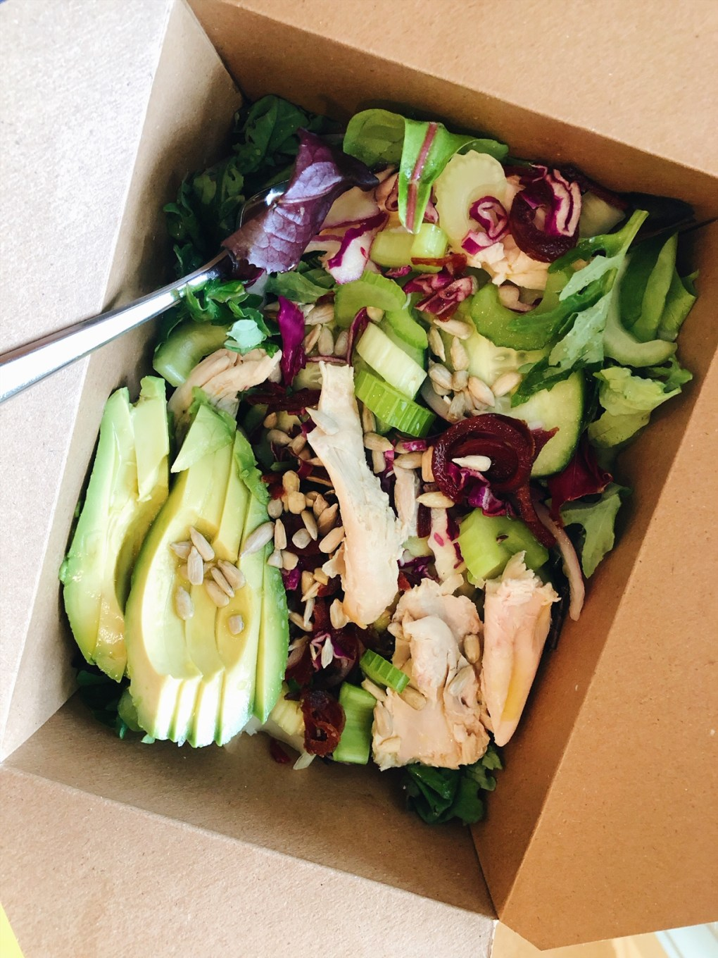 Salad in a to go container from Whole Foods with greens, celery, cabbage, beets, sunflower seeds, avocado, and chicken
