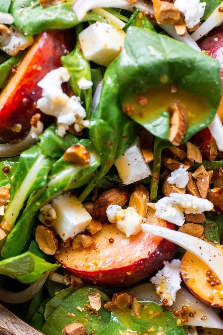 Super close up view of a green salad with peaches, chopped almonds, sliced onion, and crumbled feta cheese with mustard dressing