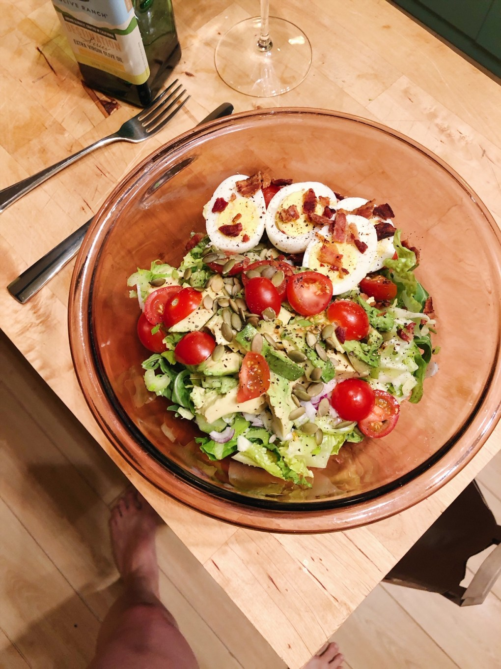 Big glass bowl of salad with hard boiled eggs, tomatoes, crumbled bacon, and pumpkin seeds on a wooden kitchen island next to a fork and knife.