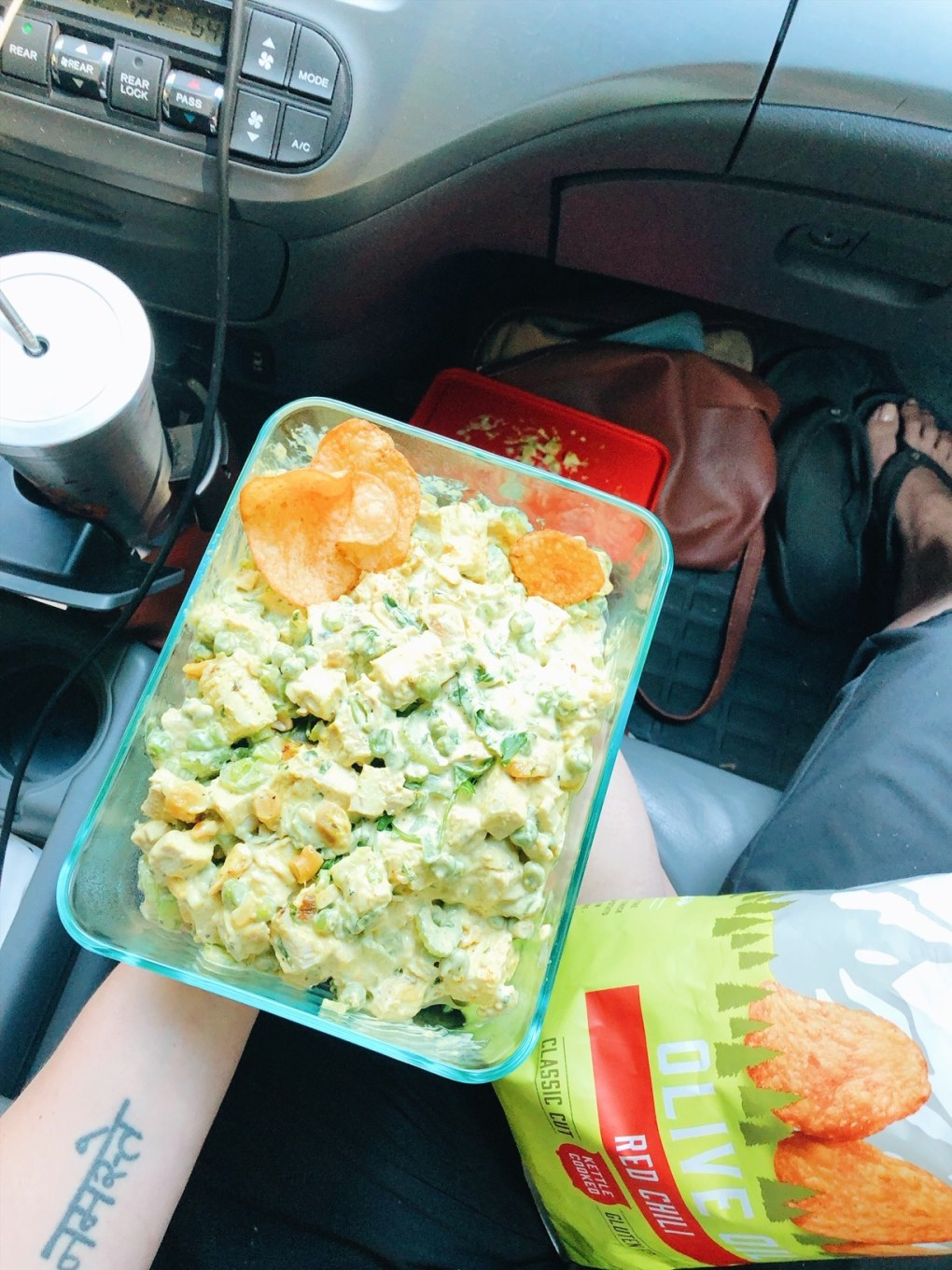 A person sitting in a car holding a glass tupperware with curried chicken salad and potato chips