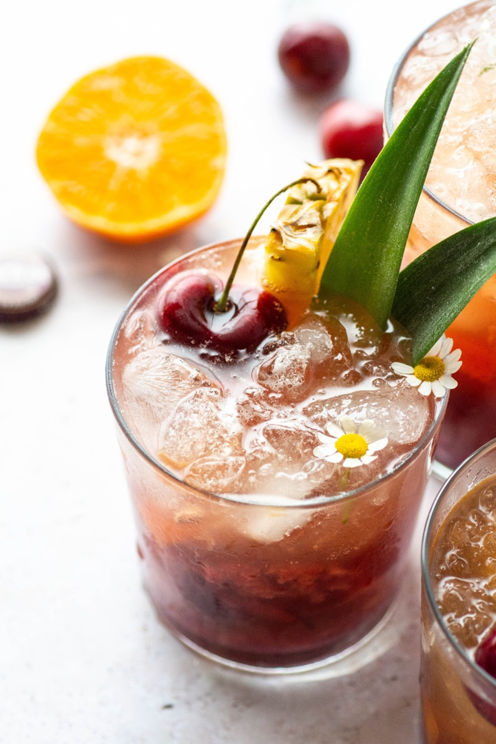 Side view of three tropical kombucha cocktails next to each other with pineapple leaves, pineapple wedges, dark cherries, and sliced tangerine on a light background