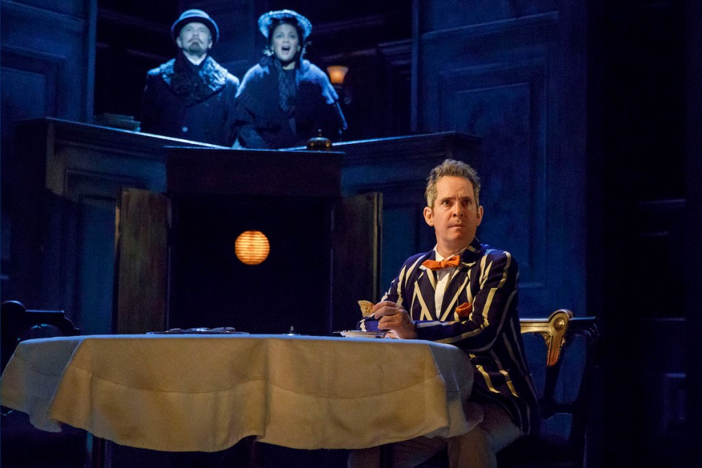 Tom Hollander, with Mr. and Mrs. Lenin looking on, in Travesties. Photo: Joan Marcus