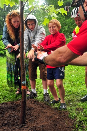Lori planting a tree with her boys on the Tour.
