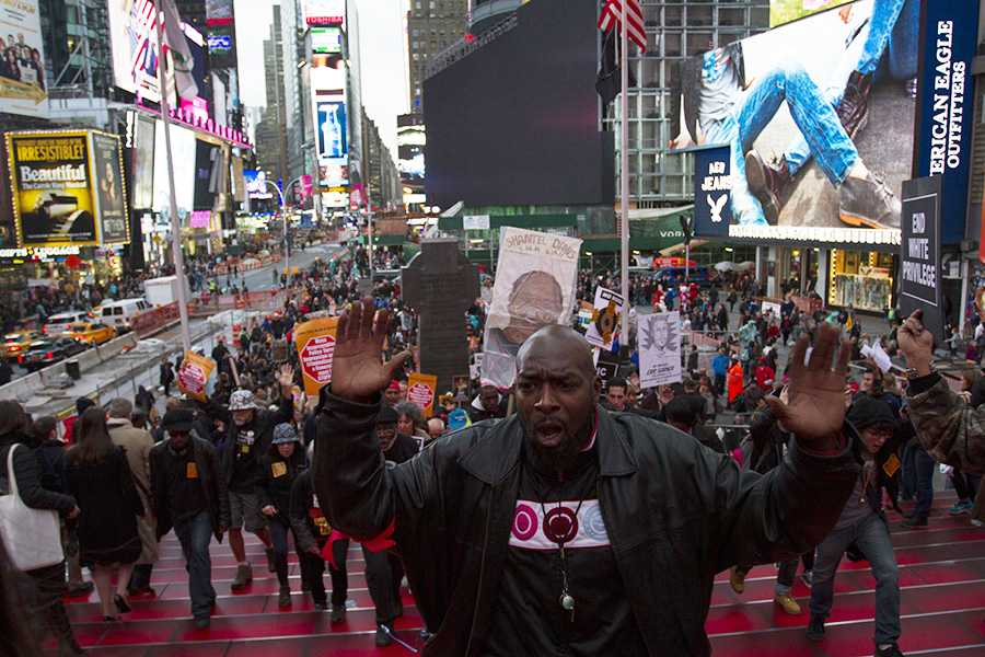 A man leads the Oct. 22 Day of National Protest up the steps in Times Square.