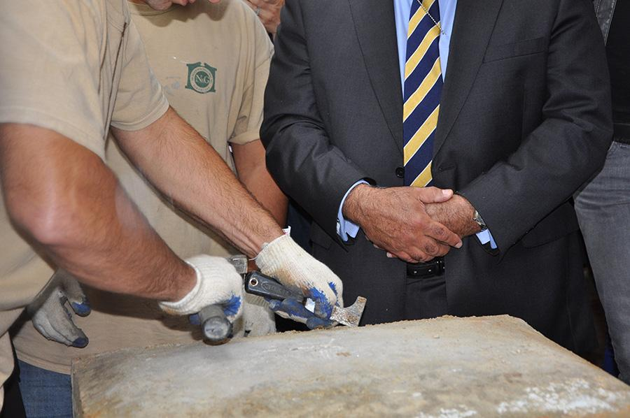 A construction worker opens the capsule with a hammer and chisel.