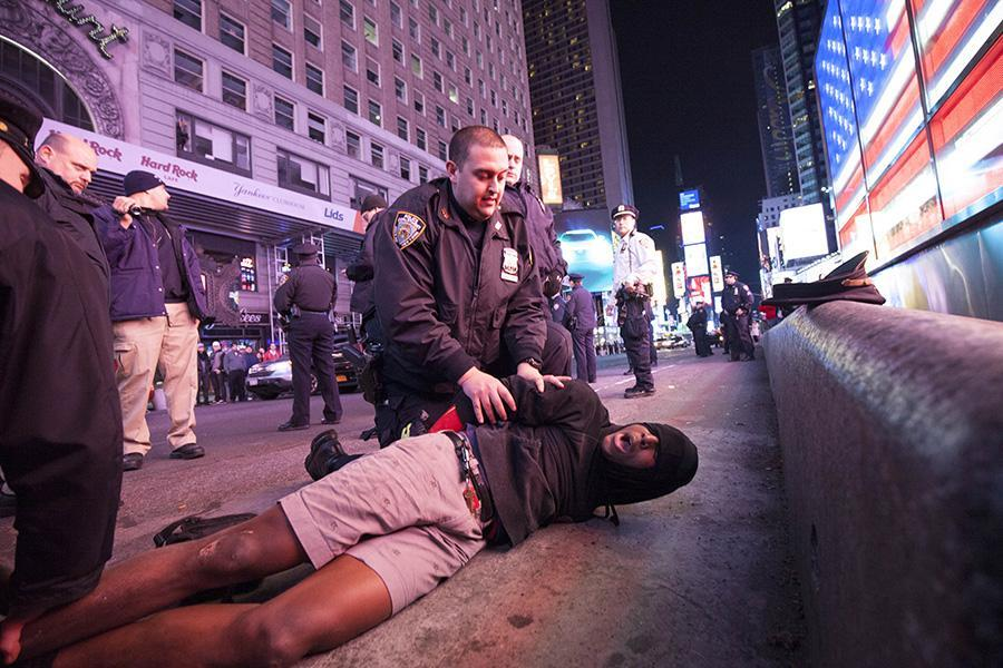 A demonstrator is restrained by police in Times Square.