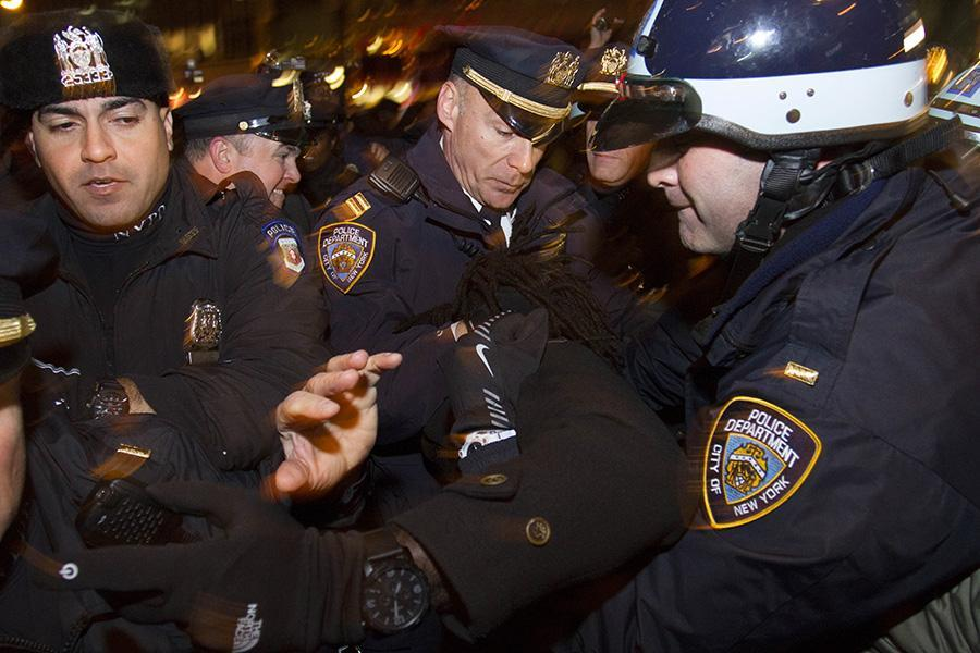 Four police officers restrain a protester.