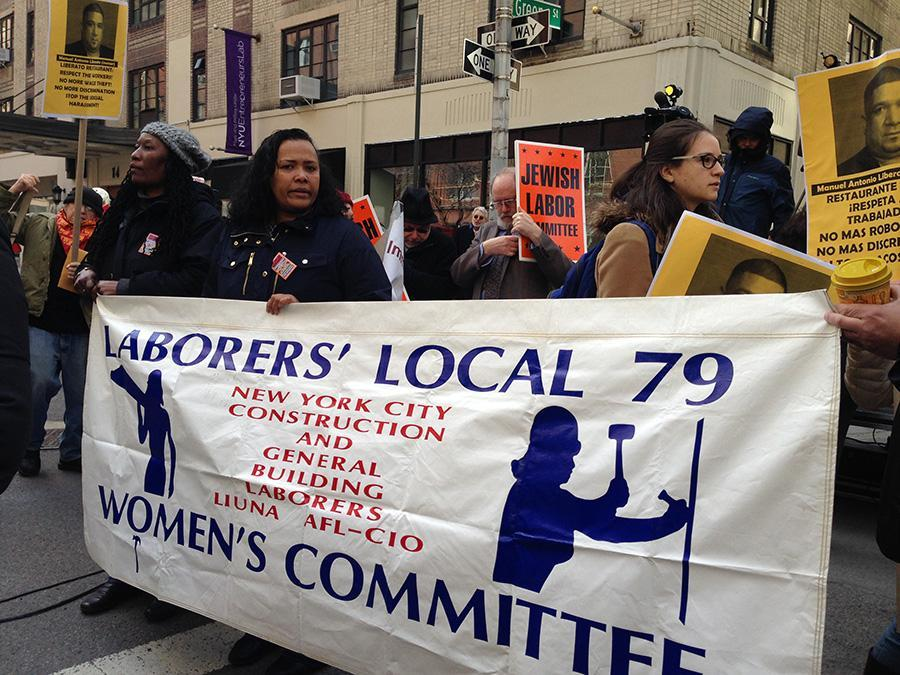 The Laborers' Local 79 Woman's Committee hold their banner alongside other labor groups.