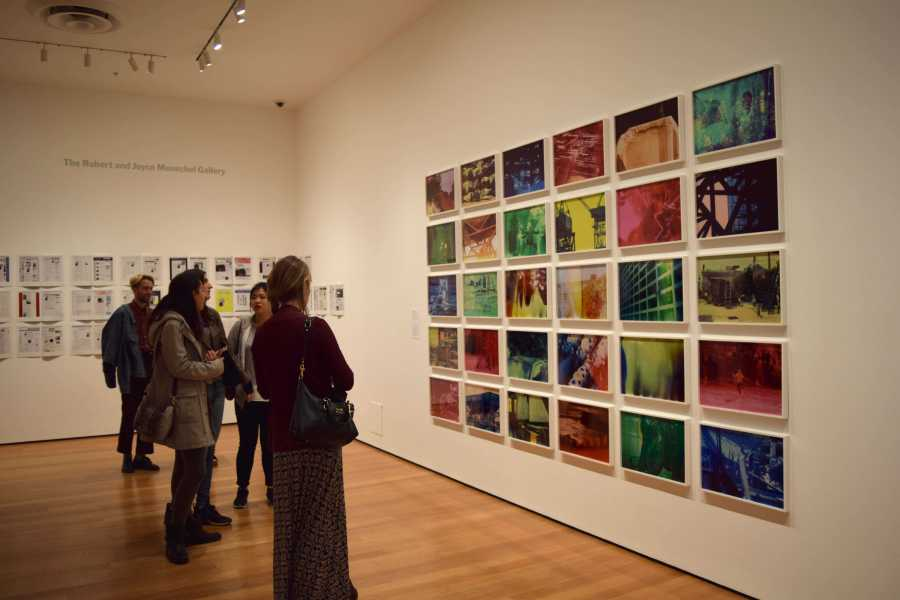"""Museum visitors look at Egyptian photographer Basim Magdy's collection of chromogenic color prints called """"The Hollow Desire to Populate Imaginary Cities."""""""