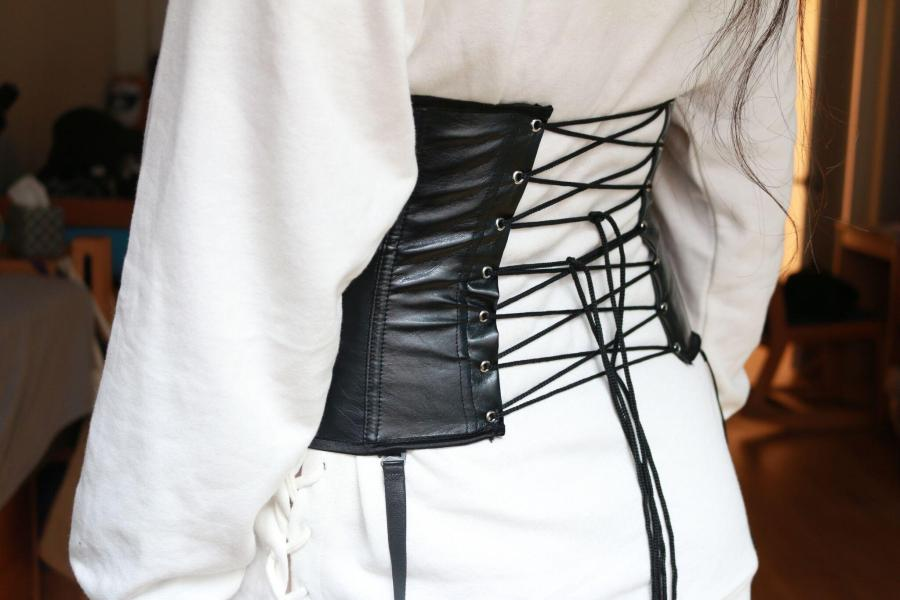 A lace-up faux-leather corset paired with a white hooded sweatshirt. Aspects of the traditional Victorian style corset have seen a revival recently, appearing on the runways of brands like Giambattista Valli.