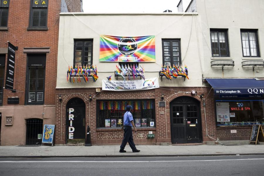 A man slowly walks past Stonewall Inn, examining its front.