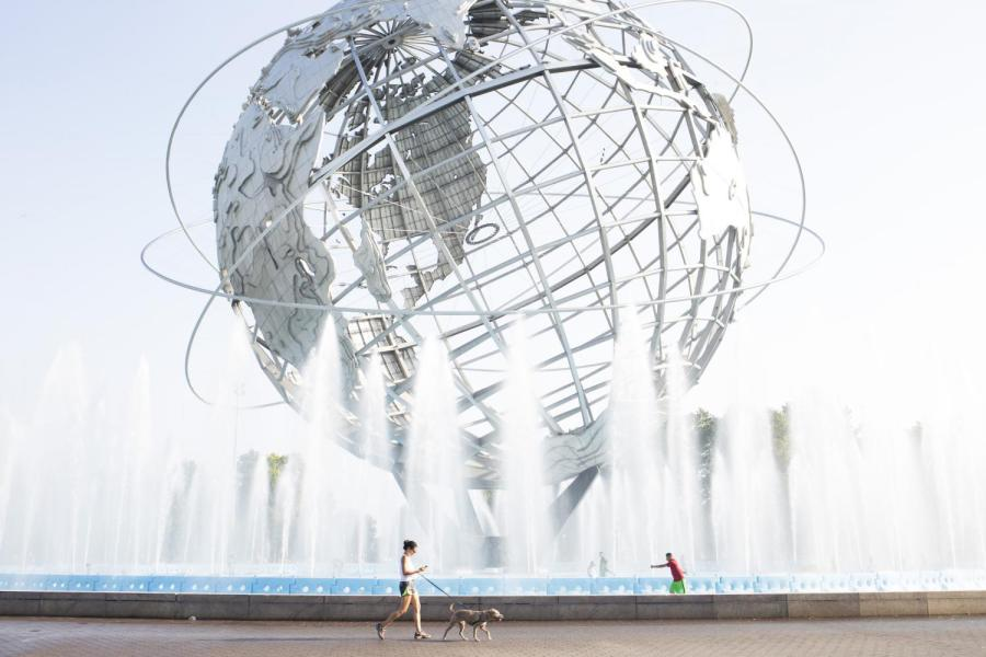A+woman+walks+her+dog+past+the+Unisphere+in+Flushing-Meadows+Corona+Park+in+the+borough+of+Queens.