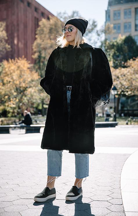 A stylish New Yorker sports a faux fur coat in Washington Square Park.