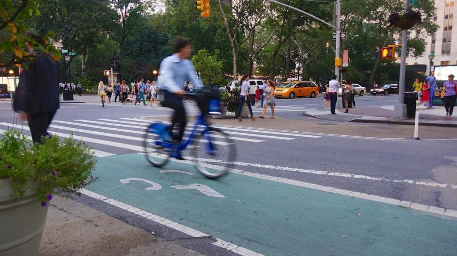 A cyclist bikes past on a Citi Bike. There are many Citi Bike locations on the NYU campus, as well as normal bicycle racks and NYU-specific racks.
