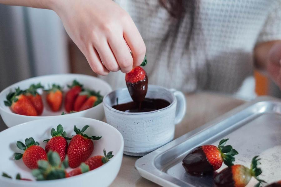 An NYU student makes chocolate strawberries in preparation for Valentine's Day.