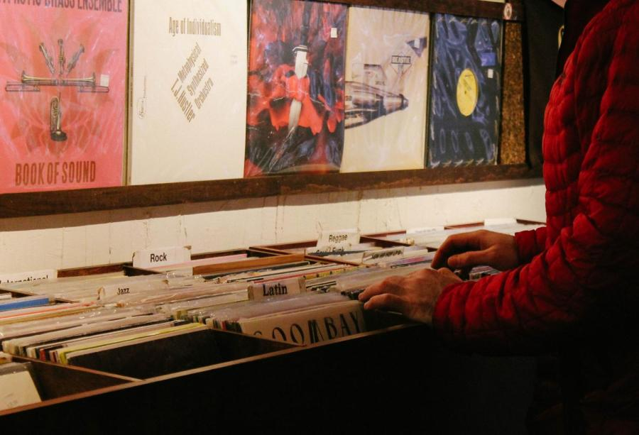 A customer browses through records organized by genre.