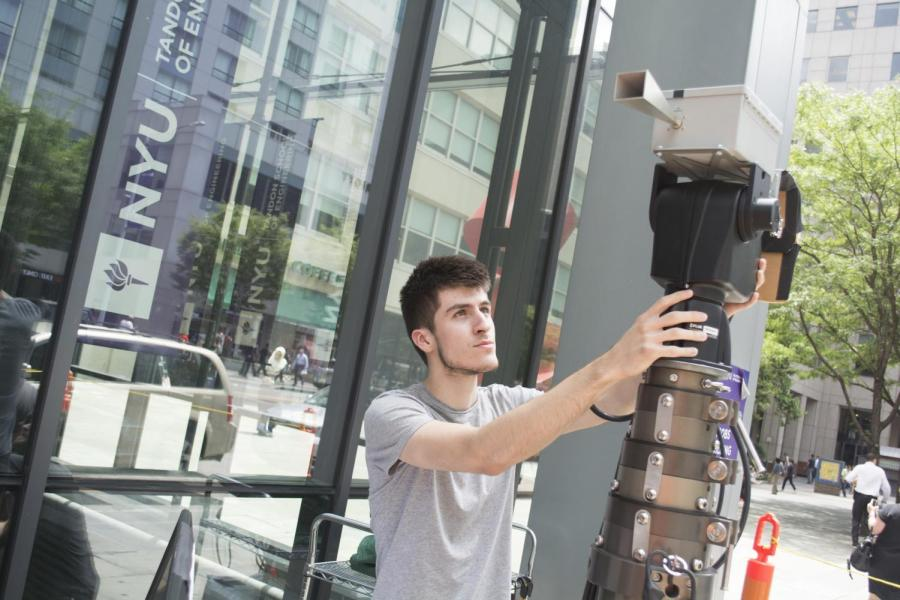 A student taking measurements of the way that millimeter waves travel and react in Downtown Brooklyn at Tandon.